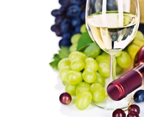 A glass of white wine and grape over white